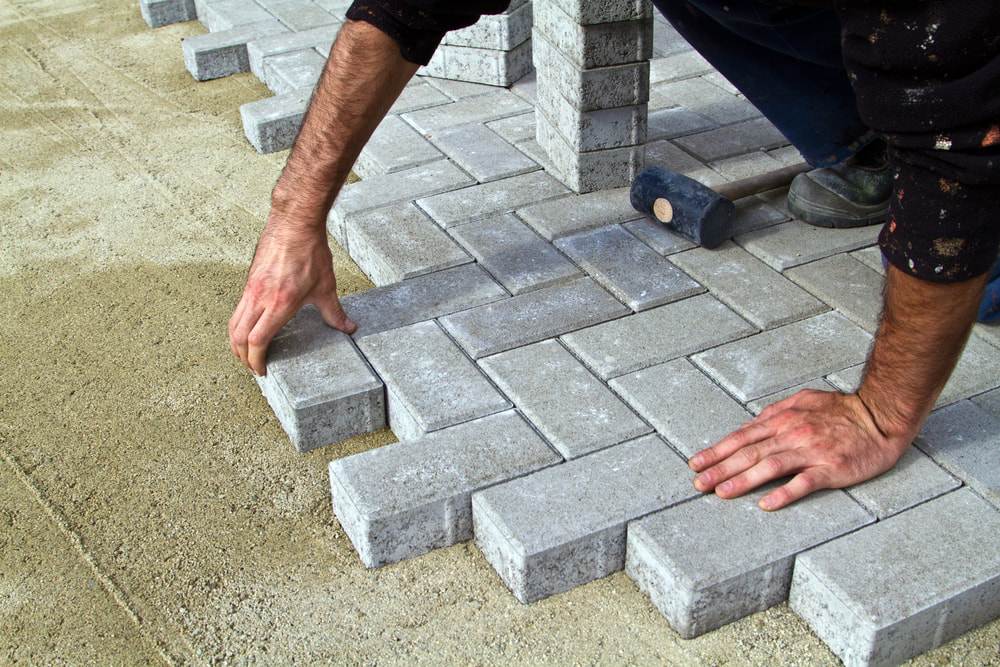 contractor placing concrete pavers during paver patio construction